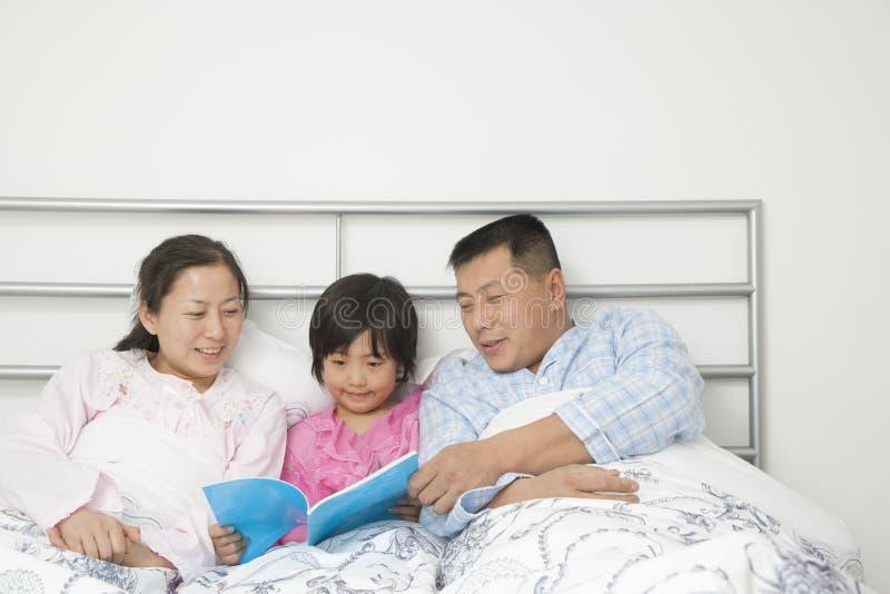 чтение семьи кровати стоковое изображение