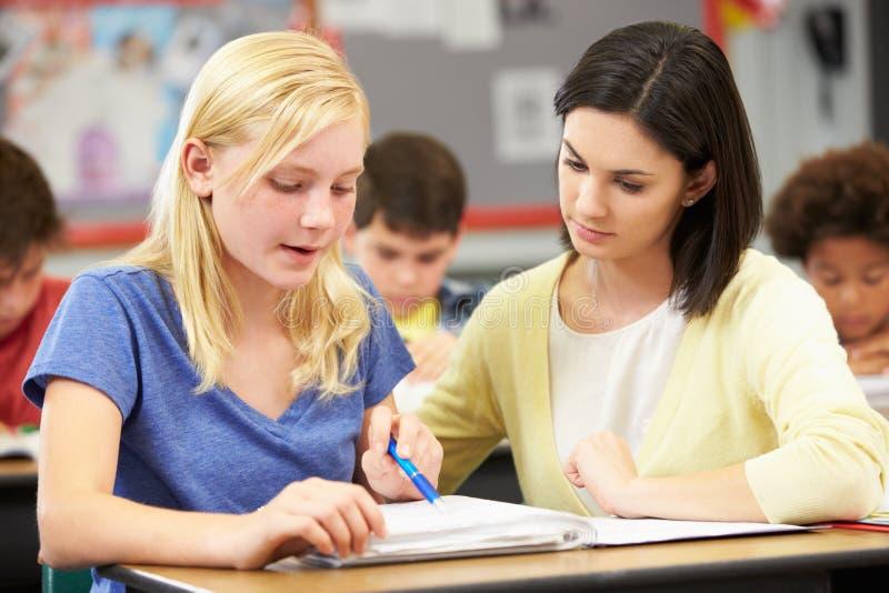 Чтение учителя с женским зрачком в классе стоковое изображение rf