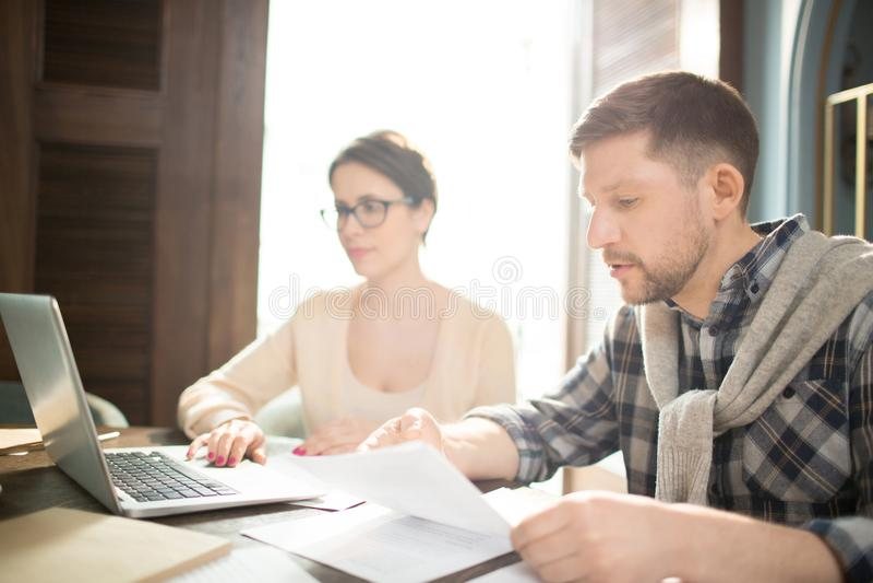 Чтение человека завертывает в бумагу около женщины с компьтер-книжкой стоковое фото rf