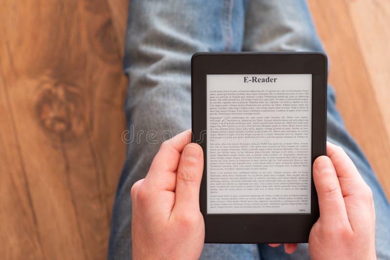 Чтение человека и eBook удержания на цифровом приборе планшета стоковое фото