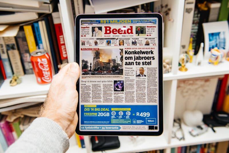 Чтение человека на iPad Pro об огне Нотр-Дам de Парижа стоковые фотографии rf