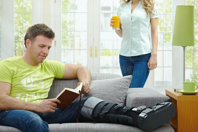чтение человека сломленной ноги книги стоковые фото