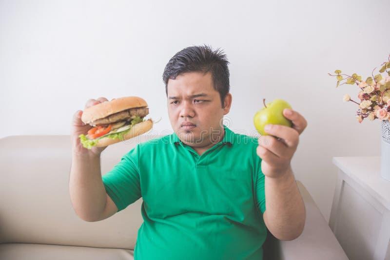 Что, который нужно выбрать между яблоком и гамбургером стоковое изображение