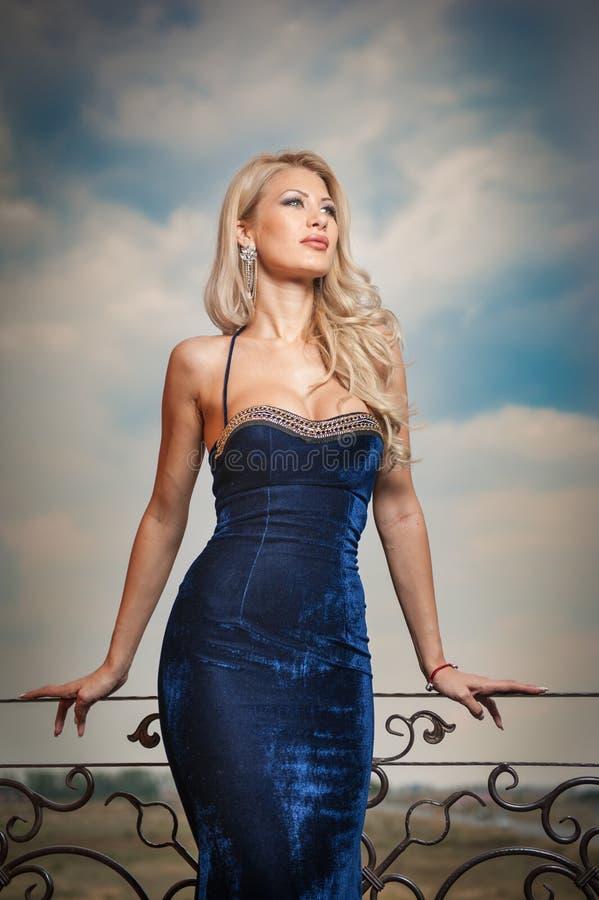 Чувственная блондинка с голубым платьем на уступе стоковые фото