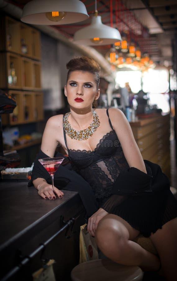 Чувственная девушка при длинные ноги и высокие пятки сидя на стуле в выпивать бара Красивая девушка с шикарным телом на высоких п стоковое фото rf