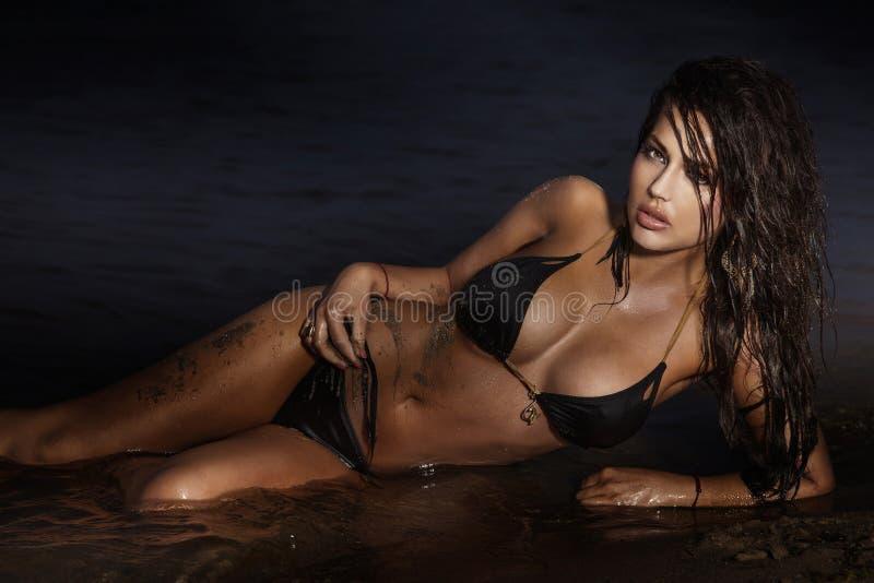 Чувственная женщина брюнет представляя на море. стоковое изображение