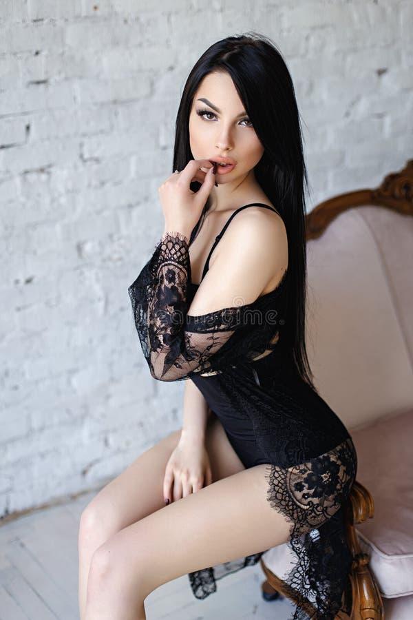 Чувственная женщина брюнет при длинные волосы, представляя в сексуальном черном женское бельё стоковое фото