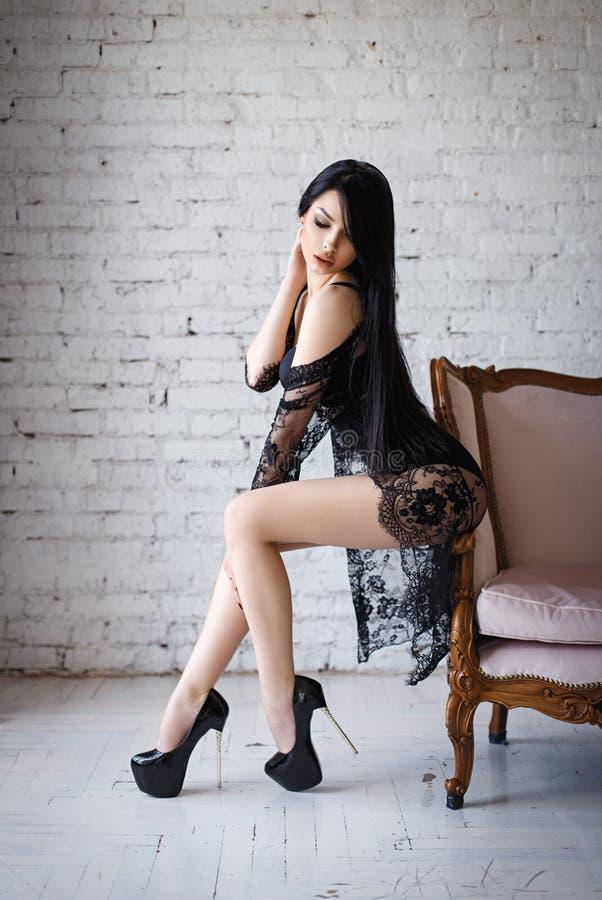 Чувственная женщина брюнет при длинные волосы, представляя в сексуальном черном женское бельё стоковая фотография
