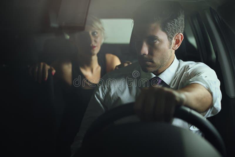 Чувственная женщина и водитель на автомобиле стоковое изображение rf