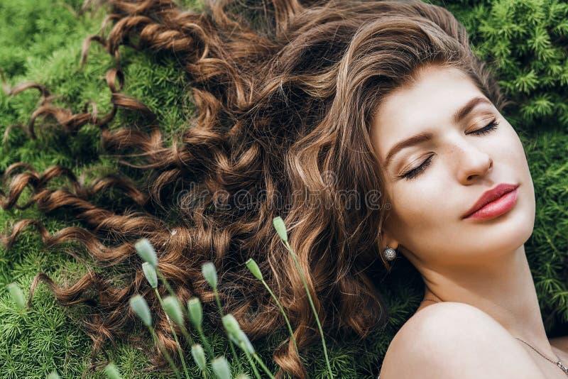 Чувственная женщина при длинные волосы лежа на зеленой траве стоковые фотографии rf