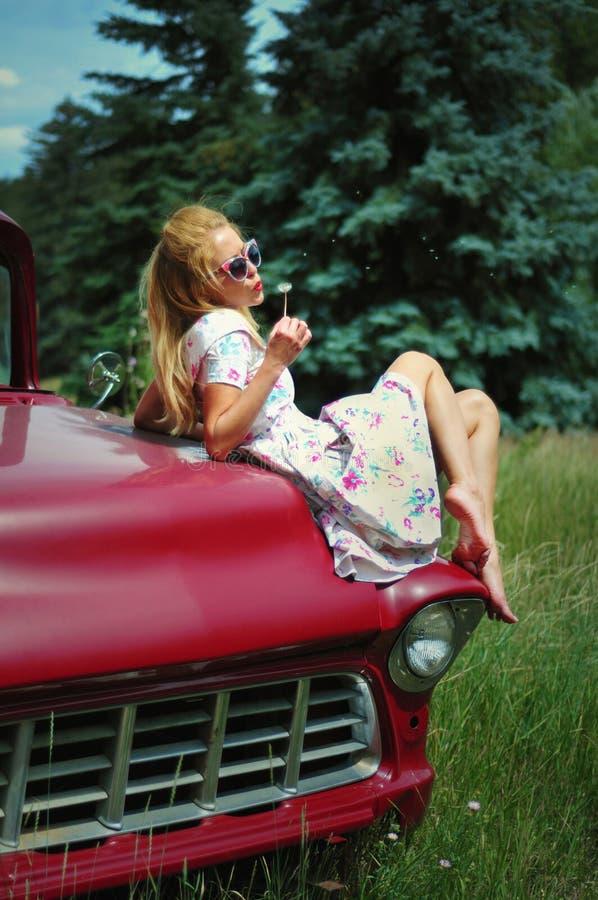 Чувственная молодая дама в винтажном платье сидя на красном ретро автомобиле стоковая фотография rf