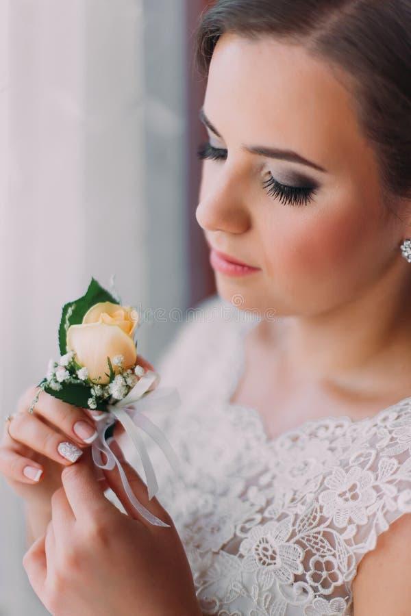 Чувственная молодая невеста представляя около окна держа милое buttonniere стоковое изображение