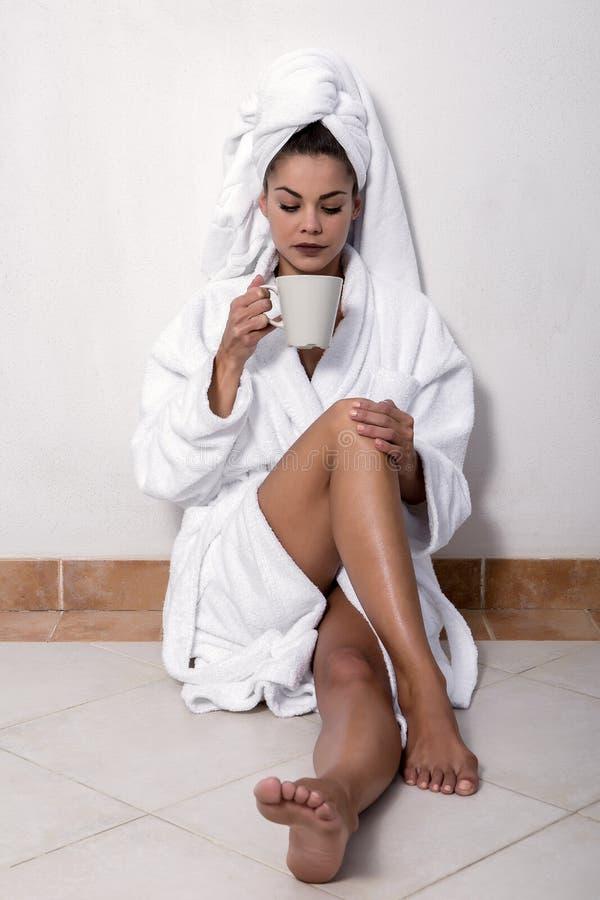 Чувственное женское усаживание на ½ ¿ floorï в купальном халате стоковая фотография