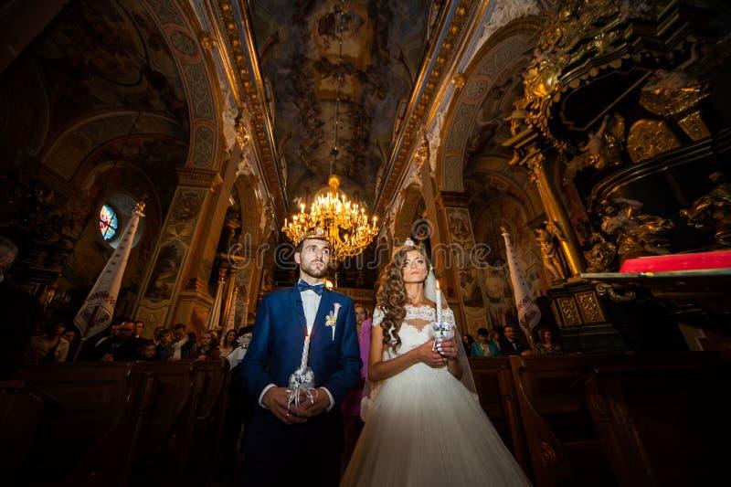 Чувственные пары новобрачных держа свечи в церков стоковые фотографии rf