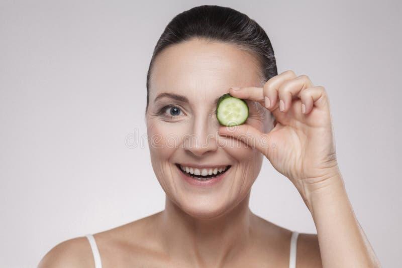 Чувствительная забота для светящей кожи Привлекательная средняя достигшая возраста женщина смотря камеру и покрывая глаз с куском стоковое изображение rf