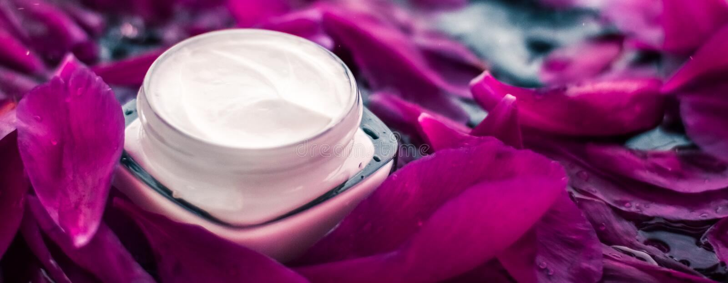 Чувствительная сливк увлажнителя skincare на лепестках цветка и предпосылке воды, естественной науке для кожи стоковое фото
