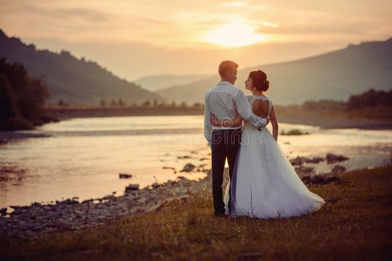 Чувствительная wedding задняя съемка Мирные красивые новобрачные обнимают и looki на одине другого на речном береге во время стоковая фотография