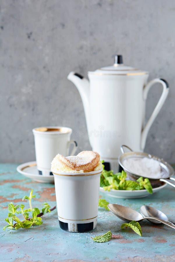 Чувствительное ванильное soufflé в ramekin с сахаром замороженности, горячим кофе и свежей мятой Очень вкусный французский десер стоковая фотография rf