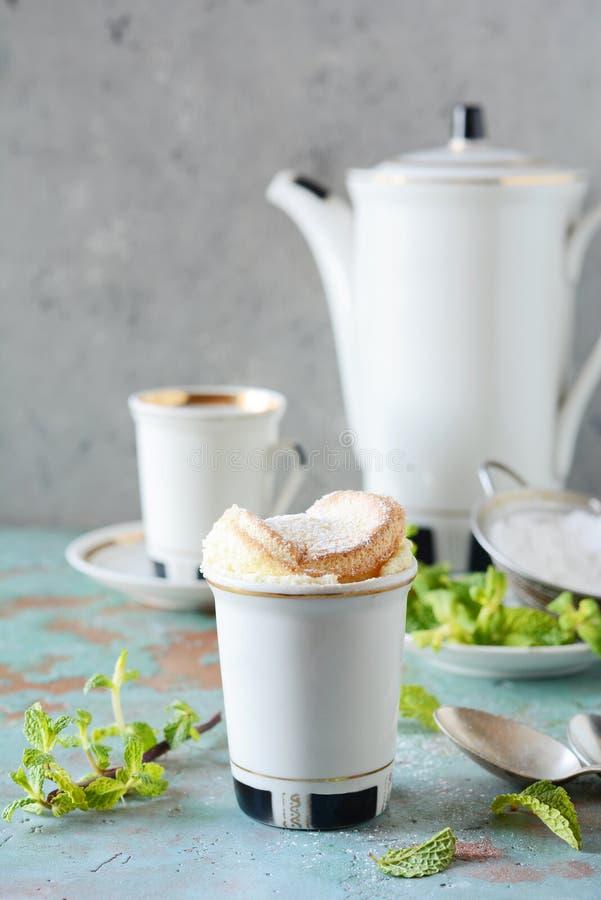 Чувствительное ванильное soufflé в ramekin с сахаром замороженности, горячим кофе и свежей мятой Очень вкусный французский десер стоковые фото