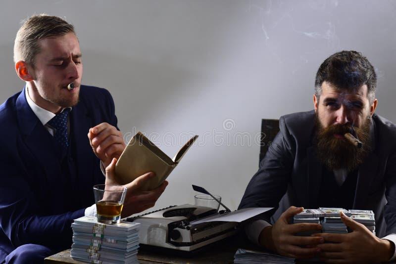 Чувствовать ослаблен Успешный вклад в деле Бизнесмены пишут финансовый отчет пока выпивающ и курящ стоковые фото