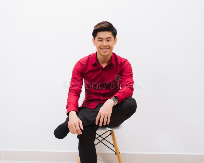 Чувствовать удобный везде Красивый молодой человек смотря камеру с улыбкой пока сидящ против белой предпосылки стоковое фото rf