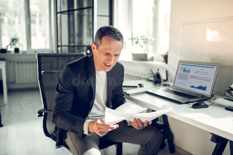 Чувство бизнесмена сердитое пока работающ на финансовом отчете стоковые изображения rf