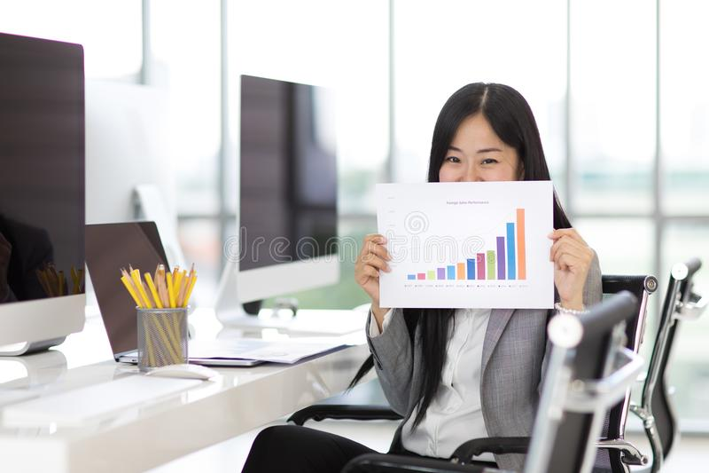 Чувство бизнес-леди счастливое и гордость показывая продажи изображают диаграммой tha стоковые фото