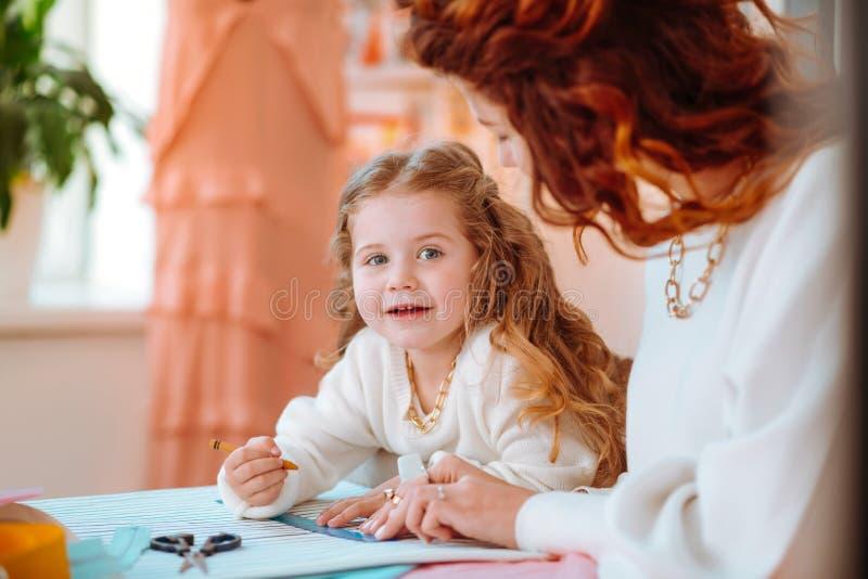 Чувство дочери радостное пока помогающ маме конструируя одежды стоковое фото rf