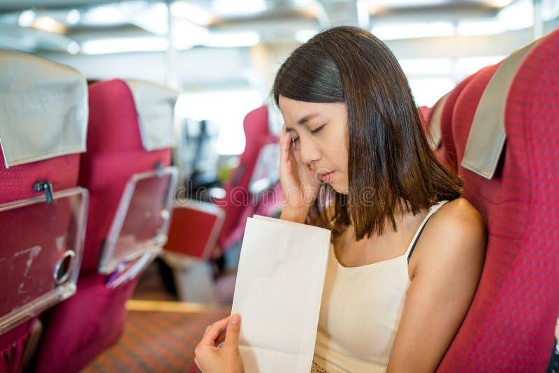 Чувство женщины нездоровое и рвота на бумажной сумке внутри парома стоковое изображение