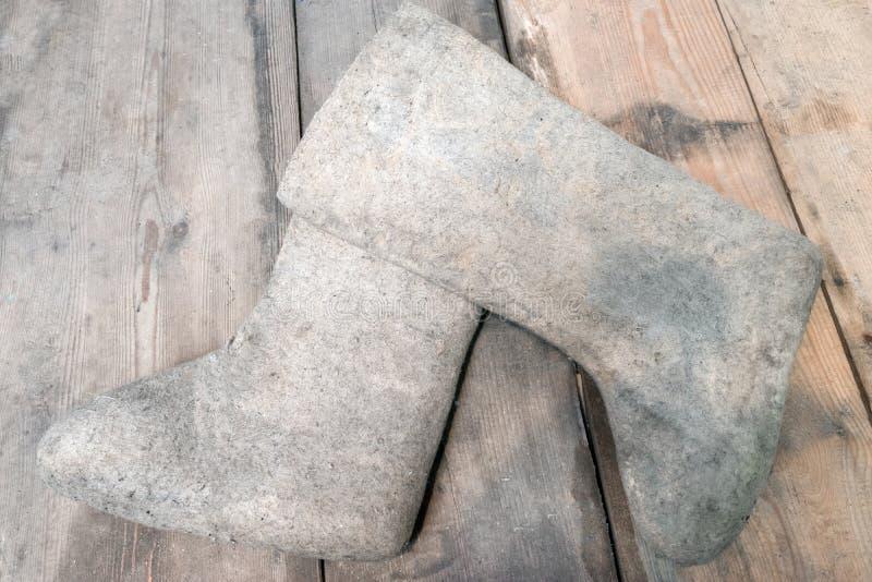 Чувствуемые ботинки на деревянном поле Обувь зимы Valenki традиционная русская в сельской местности стоковые изображения