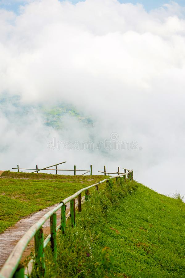 Чудесная дорожка и деревянный барьер на горном пике с белой пасмурной предпосылкой красивый путь к точке зрения стоковое изображение