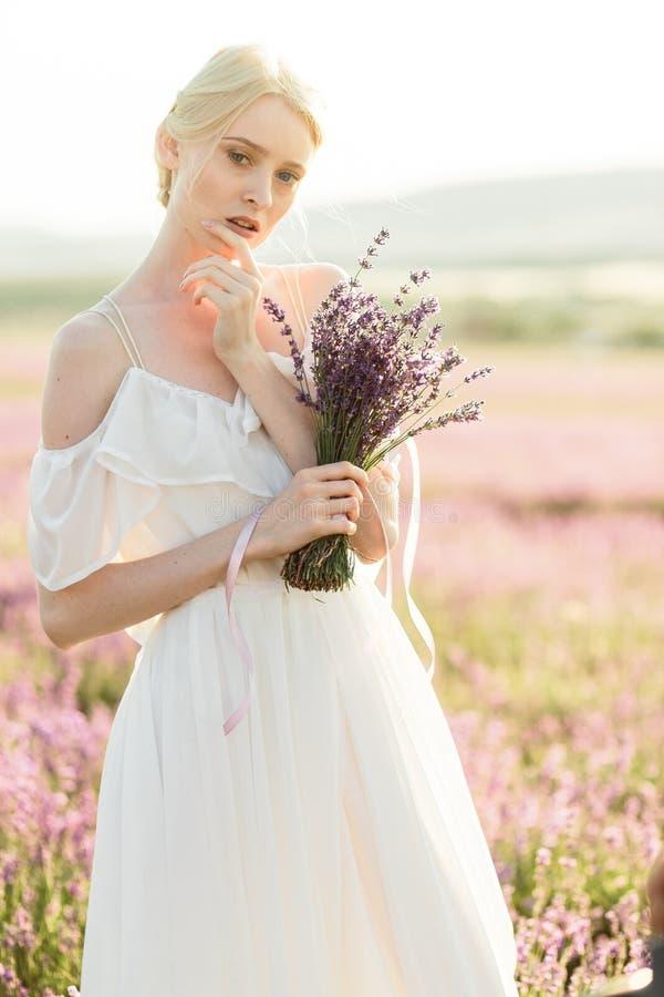 Чудесный портрет девушки в светлом платье в поле лаванды на заходе солнца стоковая фотография rf