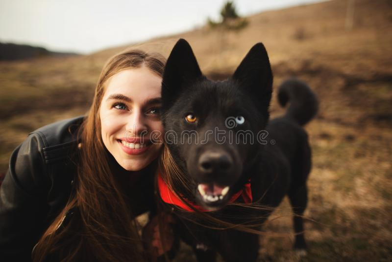 Чудесный портрет девушки и ее собаки с красочными глазами Друзья представляют на береге озера стоковое изображение