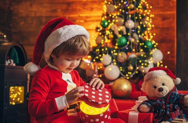 Чудо Ребенок мальчика Санта маленький отпраздновать рождество дома Прекрасный младенец насладиться рождеством Праздник семьи Маль стоковое изображение