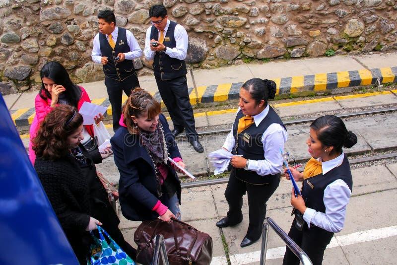 Чужие пассажиры всходя на борт туриста Perurail тренируют к Machu Picc стоковое изображение
