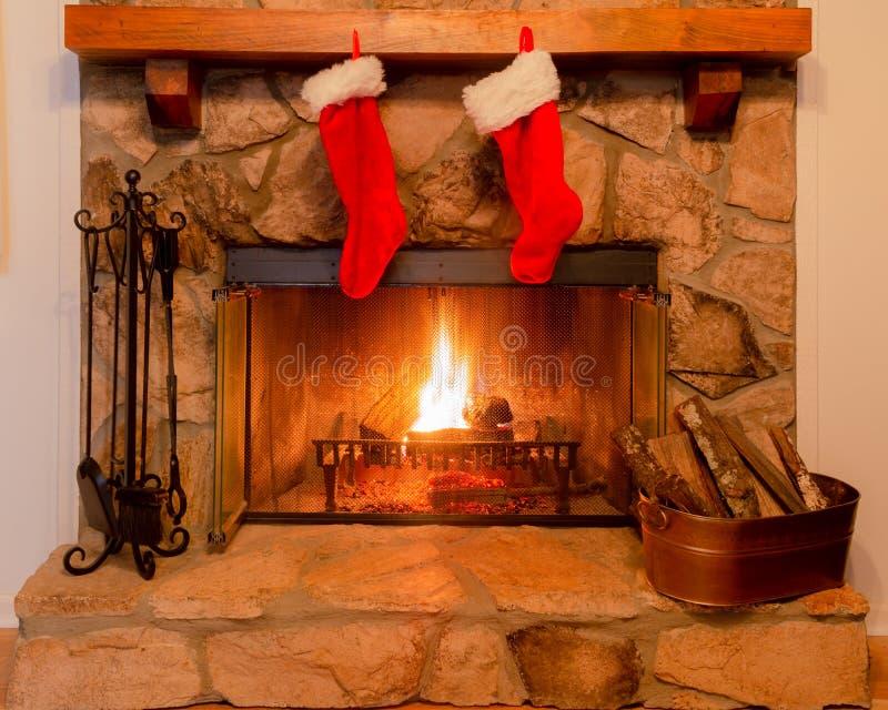 2 чулка рождества на хламиде каменного камина с теплым огнем стоковое фото