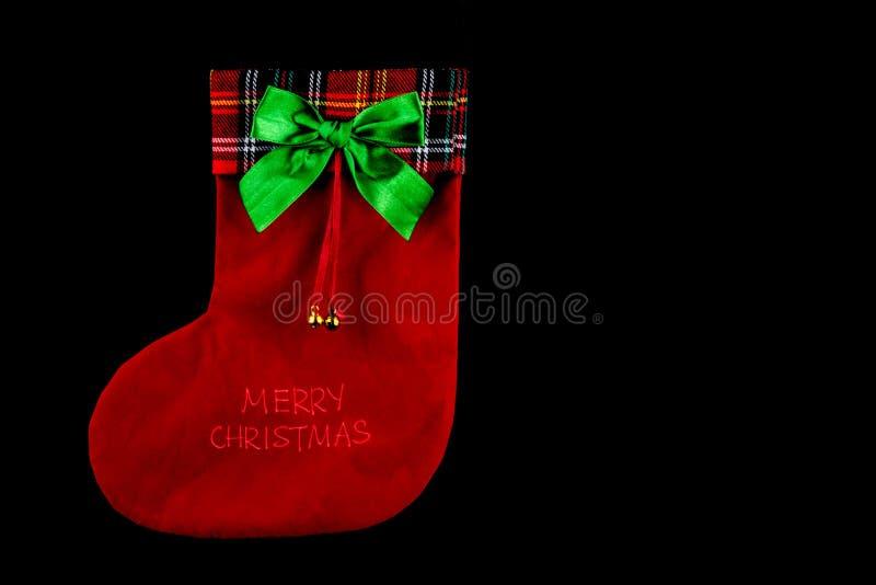 Чулок рождества с латунными колоколами и тартан на черноте стоковое фото