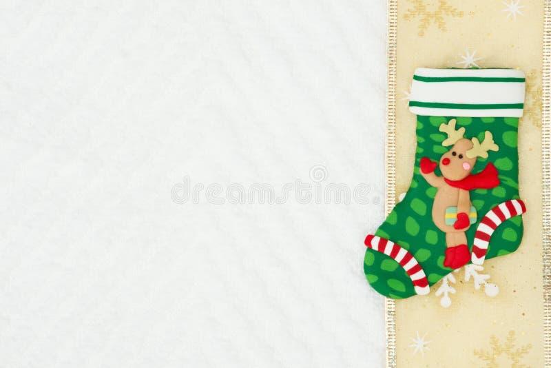 Чулок рождества с северным оленем с лентой золота на белом c стоковая фотография