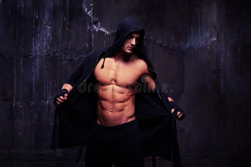 Чуть-чуть-chested мышечный спортсмен принимая черный hoodie стоковые фотографии rf