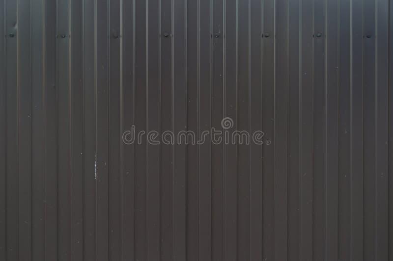 Чёрный металлический забор Кофрированный лист или профилированный лист Передняя Металлический фон Четко структурированный фон Бур стоковая фотография