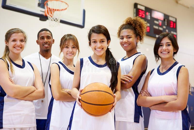 Члены женской баскетбольной команды средней школы с тренером стоковые изображения rf