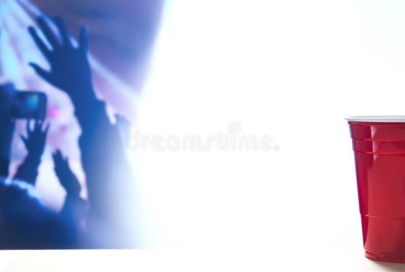 Шаблон предпосылки красной чашки партии тематический Белый фон Контейнер спирта на таблице Руки людей танцуя вверх в воздухе стоковое изображение rf