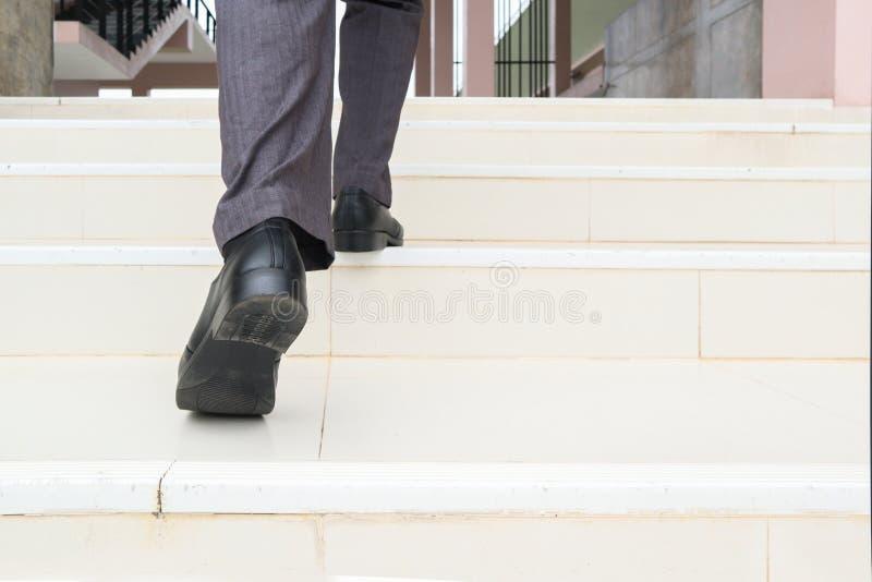 Шаг бизнесмена вверх по лестнице Нижняя часть человека в ботинках дела идя вверх по лестнице, образ жизни людей успешный и конкур стоковое фото rf