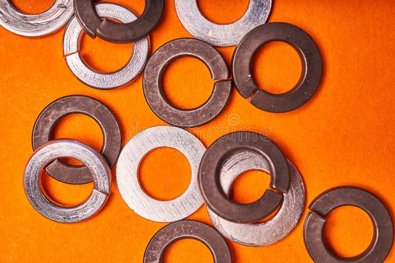 Шайбы весны на оранжевой предпосылке Элементы скрепленного болтами соединения стоковая фотография rf
