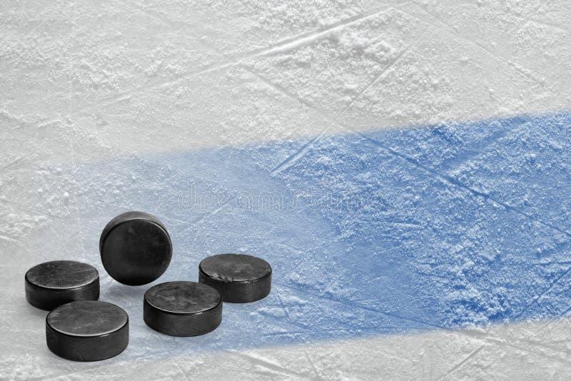 Шайбы и часть арены льда с голубой линией стоковая фотография