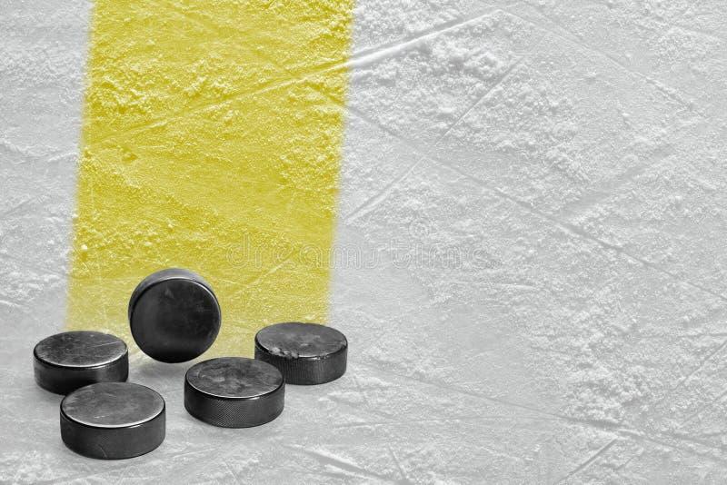 Шайбы и часть арены льда с желтой линией стоковое изображение
