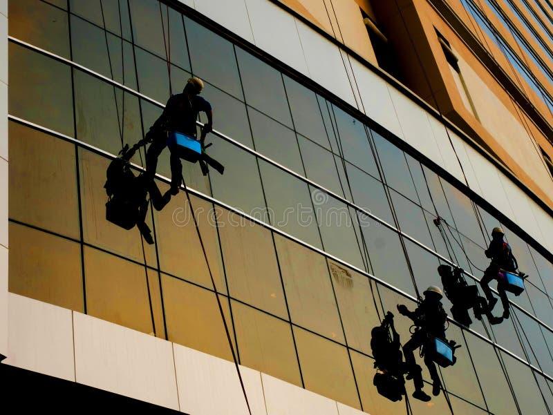 Шайбы моют зеркало окон съемки силуэта небоскреба стоковое фото