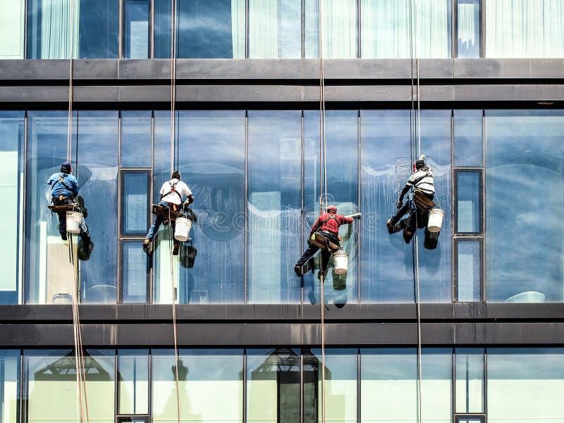 Шайбы моют окна небоскреба стоковые фотографии rf