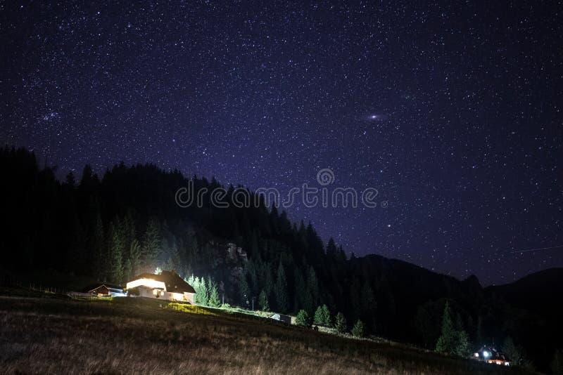 Шале под звездами, видимая галактика млечного пути, ясное небо, долгая выдержка стоковое изображение