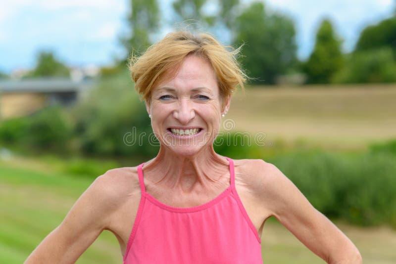 Шаловливая белокурая женщина давая притворный оскал стоковые изображения rf